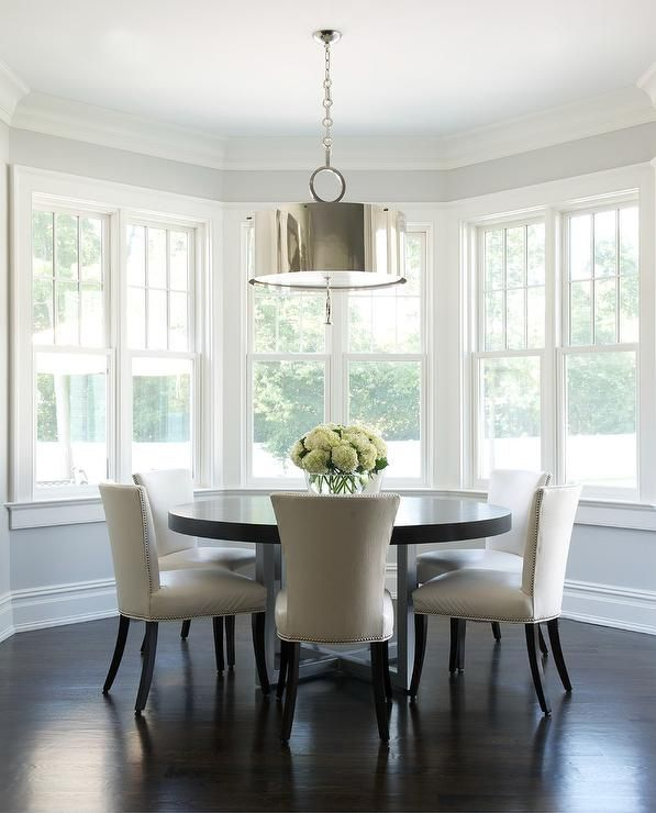 Curved Dining Room Features A Dark Stained Round Table Lined With Ivory Leather Chairs