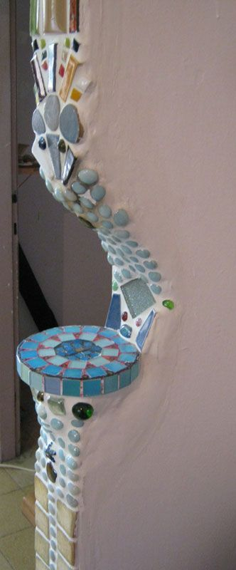 Mosaic accents in a plastered or cob wall, forming a small niche for art or a candle.