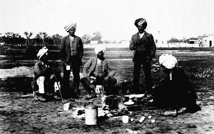 A group of Indians cooking a meal. The 'Leader' newspaper office is in the background, Jeparit c1905