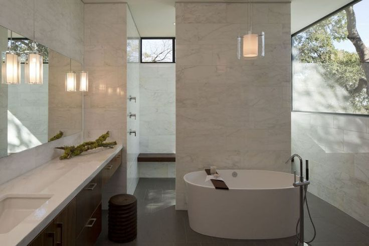 In this modern bathroom, there's a deep soaking tub and a large walk-in shower. Windows in the upper part of the walls provide light and at the same time privacy.