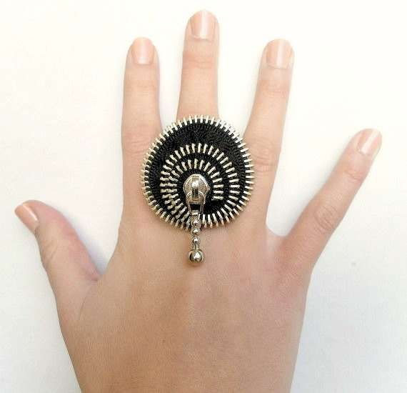LOVE THIS!  These unusual jewelry pieces by Zipper Design are made out of recycled old clothing. The zippers are taken off and remade into vintage rings, brooches, bracelets and rings that come in a variety of different colors.