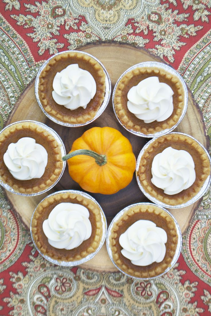 Fresh pumpkin tarts with whipped cream buttercream icing on a Ralph Lauren Thanksgiving tablecloth. By Bake Sale Toronto