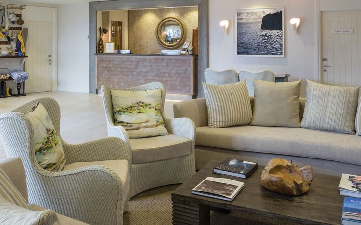 Salcombe Harbour Hotel, Devon. Hotel main reception with lounge space in front of the fireplace and soft timber hues to the Reception. Interior architectural design by DO Design Studio Ltd.