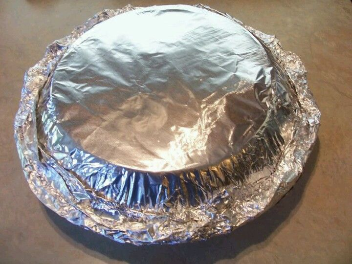Mini oven for cooking biscuits over a camp fire. Two pie pans joined together either foil. Remember to grease the bottom one and do not put over direct heat.