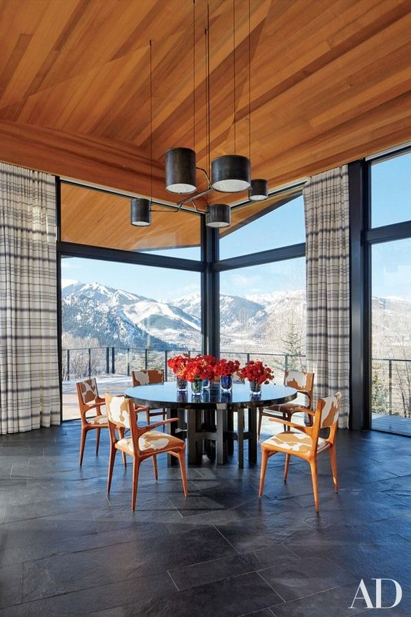 A light fixture by Atelier Van Lieshout is installed above the custom-made Ado Chale table and Carlo de Carli chairs in the dining room of architect Peter Marino's Rocky Mountain ski retreat   archdigest.com