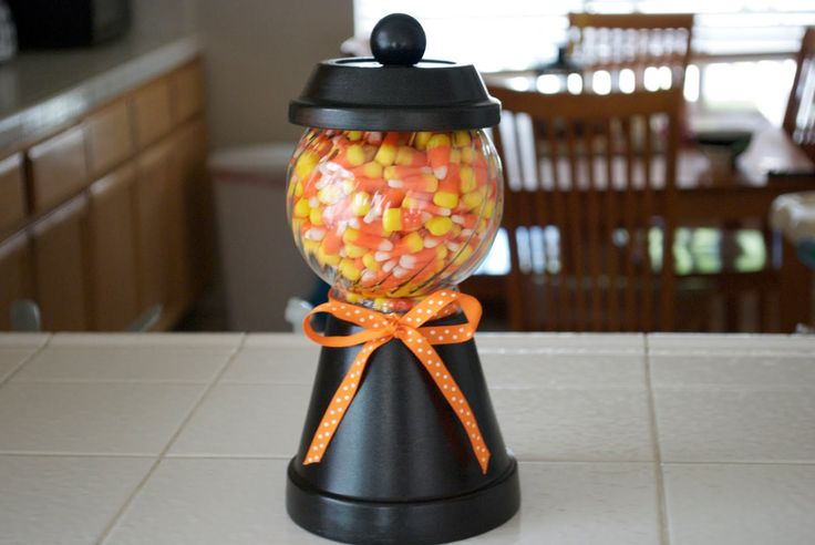 Halloween candy jar made from clay pot and saucer, glass jar and wood peg.