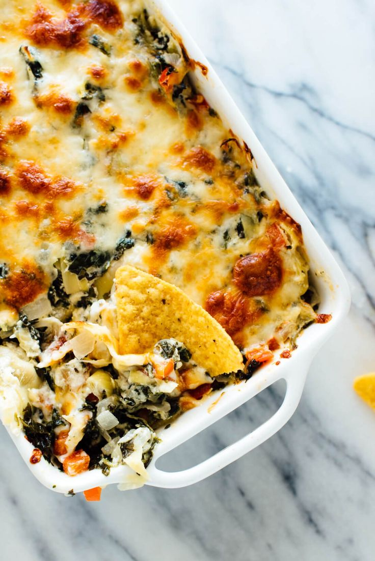 The best cheesy baked spinach artichoke dip recipe, lightened up with extra veggies and no mayonnaise! Everyone will love this delicious appetizer recipe.