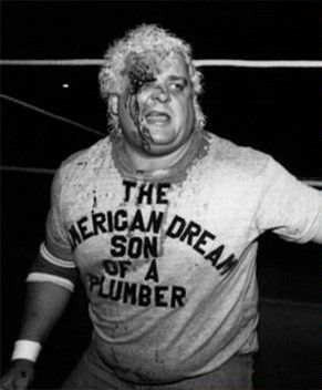 "Dusty Rhodes bleeding and wearing his homemade ""The American Dweam Son of a Plumber"" t-shirt"