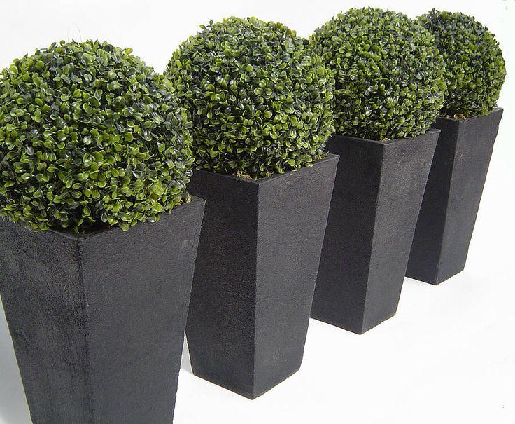 Artificial boxwood balls in black granite planters