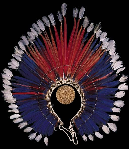 A KAYAPO LARGE FEATHER HEADDRESS  The cotton base sewn with arc of blue and red macaw feathers, white feathers at the tips, twisted cotton ties and woven fibre disc, keikru, for attachment.