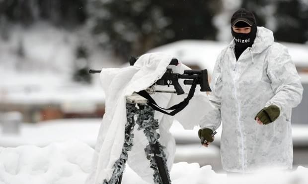 A special forces policeman covers his rifle on the roof of the Congress Centre on the eve of the Annual Meeting of the World Economic Forum, in Davos, Switzerland. Source: Laurent Gillieron/EPA