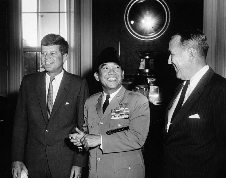 1961. 12 Septembre. By Abbie ROWE. President John F. Kennedy stands with President Ahmed Sukarno of Indonesia (center) and Under Secretary of State Chester B. Bowles (right) during a meeting of representatives from the Belgrade Conference of Non-Aligned Nations in the Red Room, White House, Washington, D.C