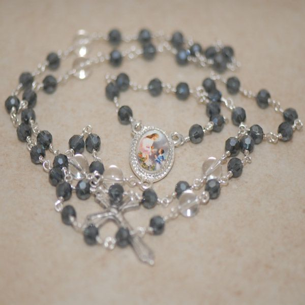 Naofa 1st Communion Rosary - Paters (Our Father beads) of 8mm smooth round clear quartz rock crystal and Aves (Hail Mary beads) of 6mm faceted charcoal grey crystal create a striking contrast in this attractive handcrafted rosary.  Each crystal is hand wrapped with tarnish resistant silver plated wire using the traditional Rosary wire wrapping technique.