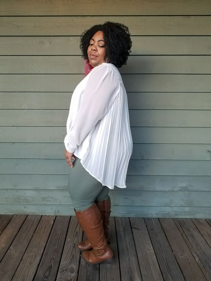 Plus size model in flowy blouse in ivory, olive jeggings, and tall brown riding boots.