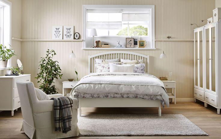 Ein Schlafzimmer mit TYSSEDAL Bettgestell in Weiß, zwei Ablagetischen, einer Kommode und zwei Kleiderschränken in Weiß