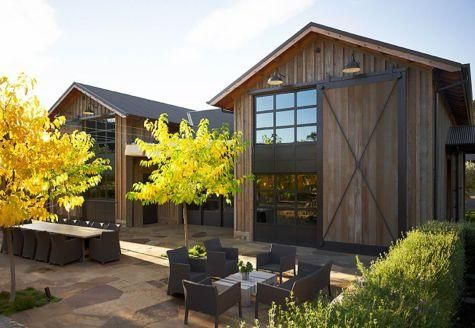 The composition of the window and door bring a Japanese element to the tall barnlike structures, while natural stone floors extend out to the patio and terrace areas from inside.