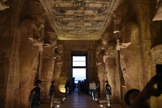 This file photo taken on October 22, 2016 shows security forces standing guard as tourists gather inside the temple  of Abu Simbel, south of Aswan in upper Egypt, to witness the sun illuminate the statue of Ramses II. With a shaky  economy following years of unrest and a huge drop in tourists, Egypt is struggling to preserve its  fabled archaeological heritage [Credit: Mohamed El-Shahed/AFP]