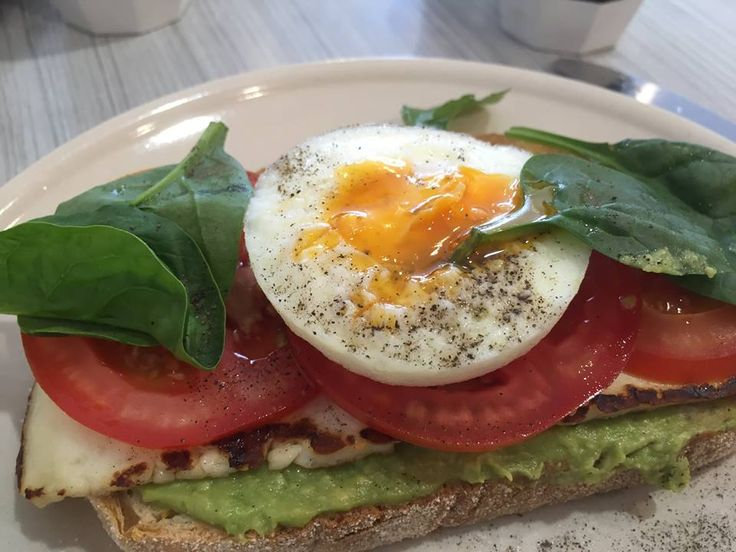 Avocado on sourdough topped with grilled haloumi, tomato, spinach leaves and a poached egg.... Yum