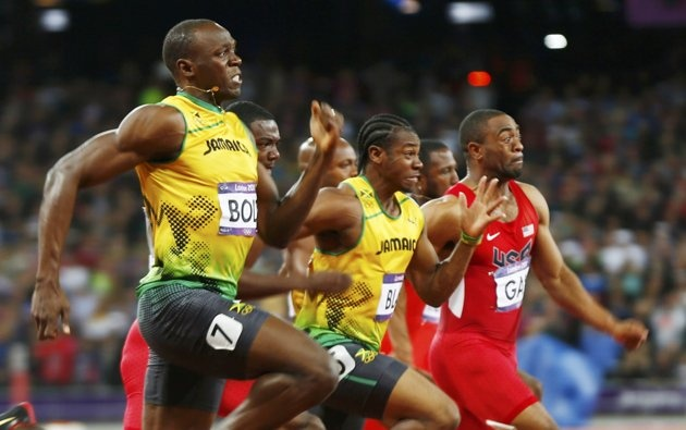 Jamaica's Usain Bolt (L) leaps ahead to win the men's 100m final past countryman Yohan Blake (C) who took second and Tyson Gay of the USA (R) who took fourth during the London 2012 Olympic Games at the Olympic stadium in London August 5, 2012. Bolt proved that lightning can strike twice by retaining the 100 metres sprint title, the most coveted of all Olympic golds, in a searing 9.63 seconds - the second fastest run of all time.