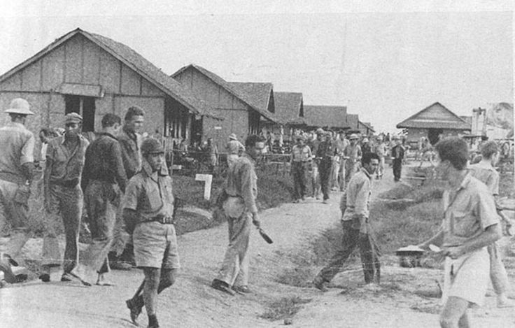 This photo shows the POWs at Camp O'Donnell receiving their rations. The food was given in meager portions. Note the Japanese guard walking among the prisoners.  The POW directly behind the guard, and walking in the same direction as the guard, is Jim Bashleben of B Company.