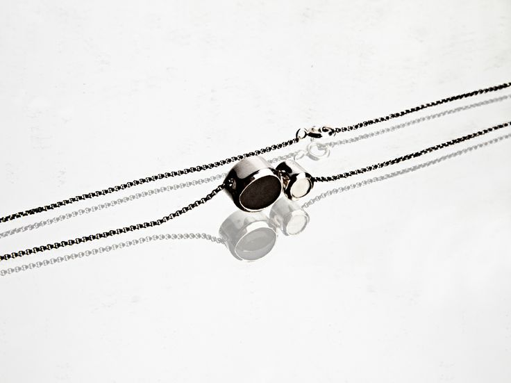 necklace with 2 little pendants; patinated silver , porcelain set on silver..a black one and a white one