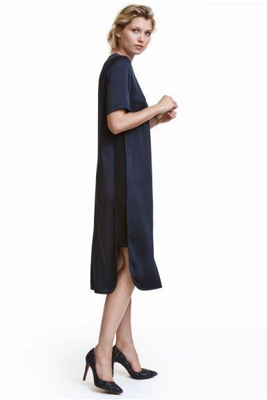 Платье длиной до середины икры: Платье длиной до середины икры прямого кроя из ткани с легким блеском, ниспадающей тяжелыми складками. Короткие рукава и матовые вставки по бокам. Скругленный нижний край, по бокам разрезы. Вырез с пуговицей сзади у горловины. Без подкладки.