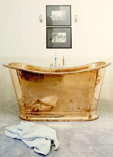 brass tub with black and white framed prints, edison bulb sconces, bathroom,