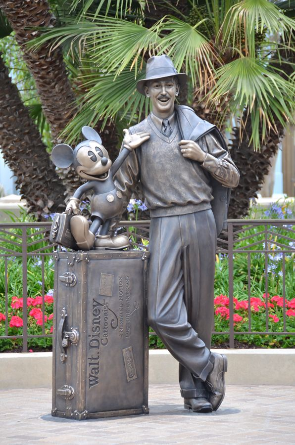 """""""Storytellers""""—this statue was placed at street level and depicts Walt Disney as a humble, optimistic young man dreaming of achievements yet to come. Walt in dressed in a fedora and traveling attire, depicting how he and Mickey had just arrived off the train from Missouri with all of their belonging in one small trunk."""