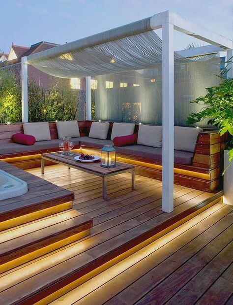 Diseño de terraza con un cómodo sofá, suelo de madera y luz indirecta