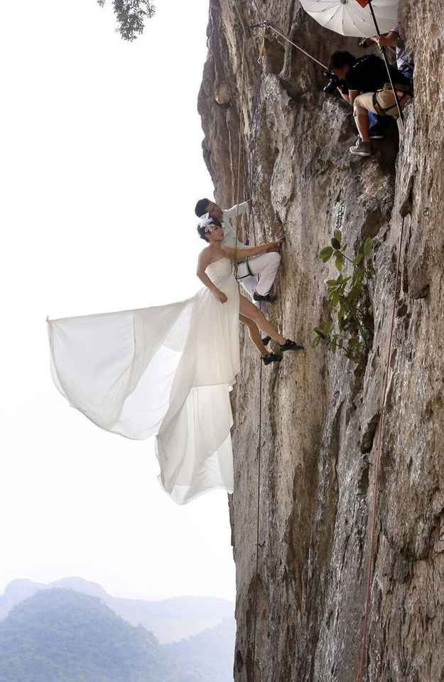 Fang Jing and her new husband, surnamed Zhao, love outdoor sports and decided to have their wedding photos taken while rock climbing, according to local media reports. | Chinese Couple Take Wedding Photos While Rock Climbing