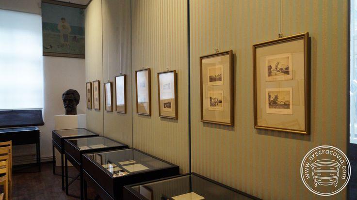 Metalowe, otwierane gabloty z oświetleniem na tle tapetowanych paneli wystawowych.