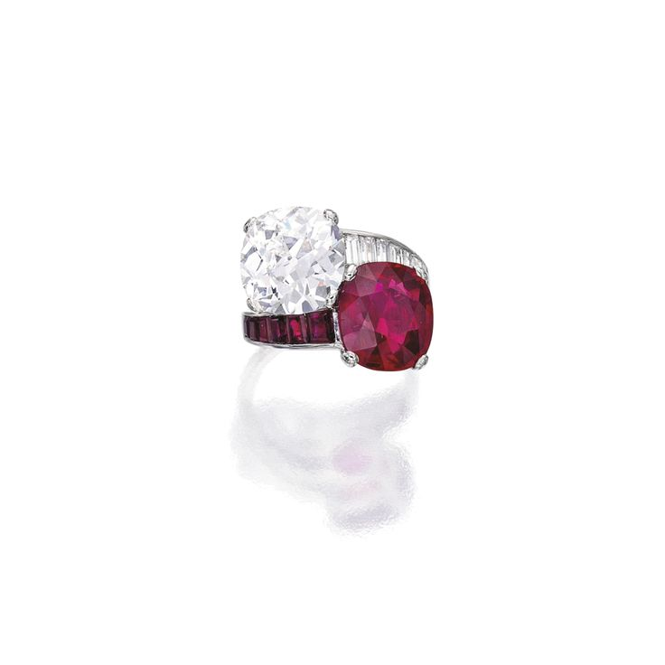 AN EXQUISITE PLATINUM, RUBY AND DIAMOND RING Of crossover design, set with a cushion-cut ruby weighing 4.45 carats and a cushion-cut diamond...