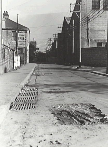 6 August 1956 Angel Street Newtown. Looking south towards King Street, half way between Norfolk and Harold Streets. Showing excavations by the Water Board. Sign on Grocer for ' Maxam Bakeo, Perfect Pastry from a Packet'.
