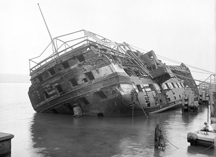 """The """"Granite State"""", sunk and listing, after burning at her pier in the Hudson River on May 23, 1921. The Granite State was formerly the USS New Hampshire, built in 1825, launched in 1864, and served as part of the South Atlantic Blockading Squadron in the Civil War."""