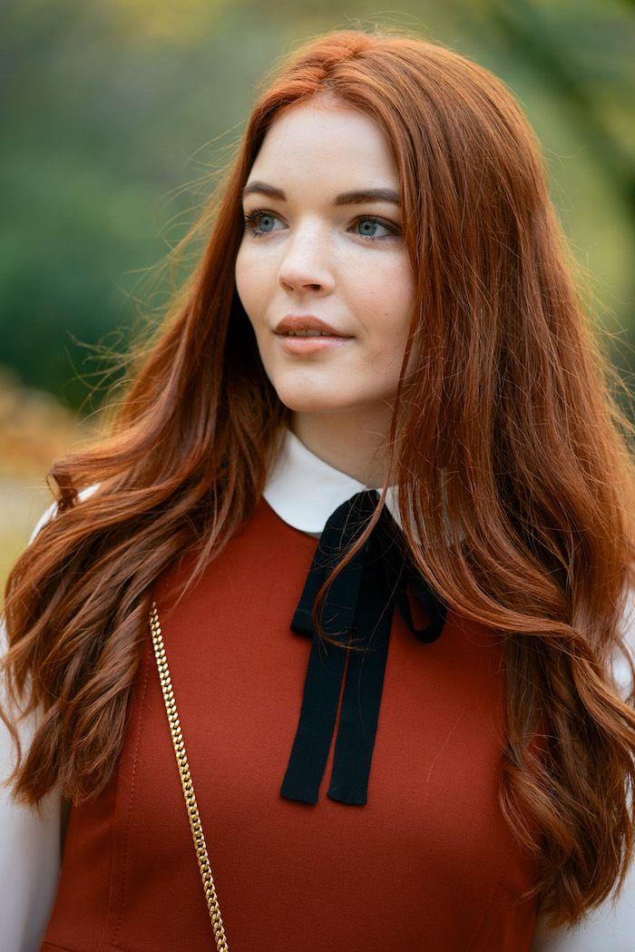 cheveux roux, robe rouge avec chemise blanche, sac à main avec bandoulière en or, coiffure avec extrémités bouclées