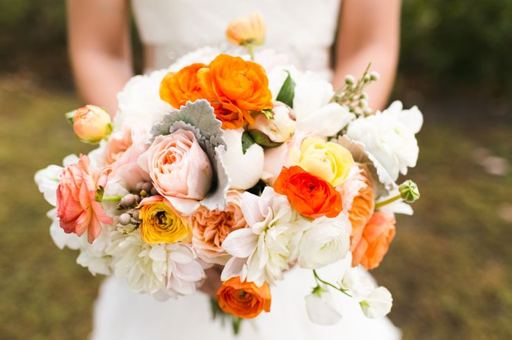 Bride's bouquet of white peonies, cafe au lait dahlias, orange, peach and white ranunculus, peach garden roses, silver brunia and dusty miller.