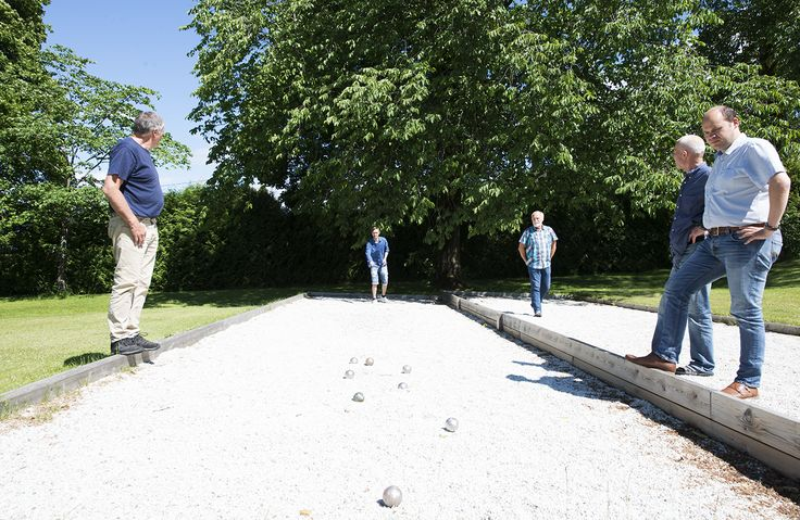 Guests using our petanque court. Having fun, enjoying hotel living, summer, spring, green garden, Norway. Hotel Refsnes Gods.