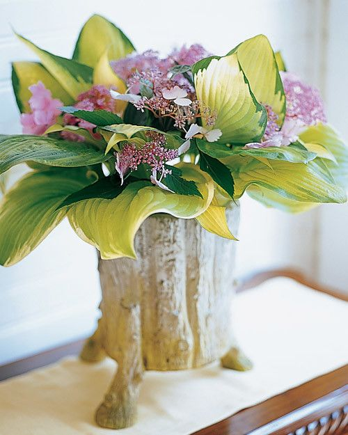 Create an arrangement of lush hosta leaves and lavender hydrangeas, fitted into a tree-trunk-inspired vase.
