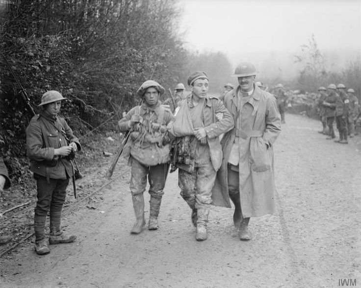 An Army Chaplain of the Army Chaplains' Department helping along a wounded German prisoner taken near Aveluy Wood on the 13th of November 1916.  The duties of military chaplains was primarily the spiritual and mental well-being of their men. However...