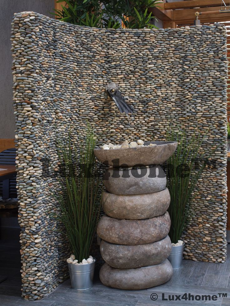 Kamienie otoczaki na ścianie - koncepcja. Na ścianie model Ścianki z Otoczaków Standing Stone Pebbles Dark Ocean 15x30 od Lux4home™. Fontanna to umywalki z kamienia polnego Lavabo Cut od Lux4home.