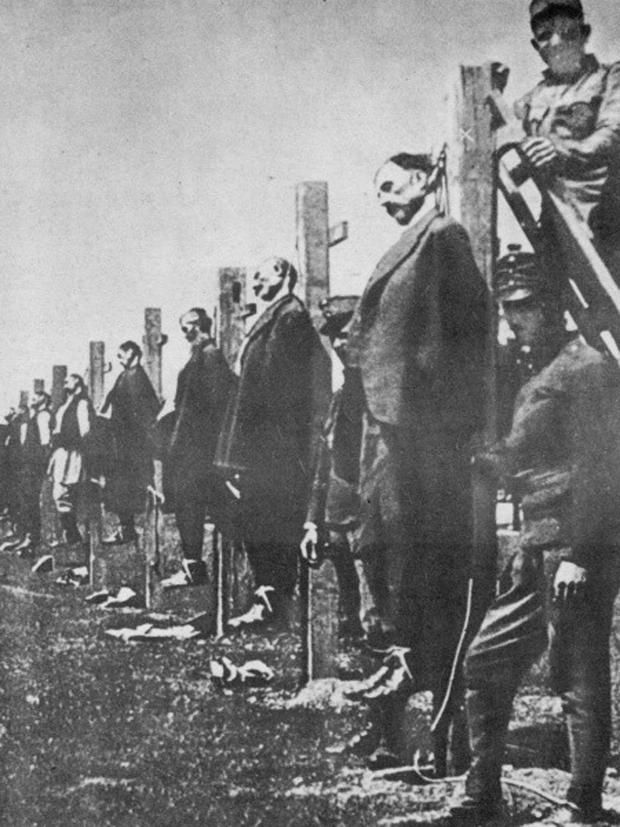 The shocking, black-and-white photograph, taken on the edge of a Serbian village just days after it was invaded by the massed forces of the Austro-Hungarian army in the late summer of 1914, is not the only one of its kind. In this one, a line of Serbian men in civilian clothes are attached to posts: possibly dead already, possibly awaiting execution by firing squad.