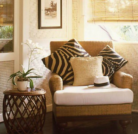 British Colonial Style - mixing here light walls with dark flooring, warm tones in the chair coupled with the strong animal print cushions and the pale seat cushion. The black framed picture on the wall, the cane side table and the plant accessories.