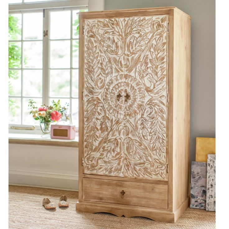 Vandara solid mango wood wardrobe hand carved with lotus flower and leaf motifs and finished with a whitewash. This 2-door wardrobe has a full-width rail, a removable shelf & a useful lower drawer.