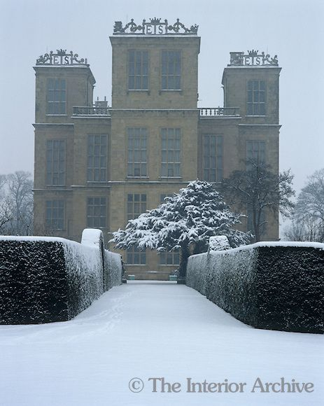 A snow-covered path leading to Hardwick Hall. The initials 'ES' on the tower parapets refer to Elizabeth Shrewsbury, aka Bess of Harwick, the original owner
