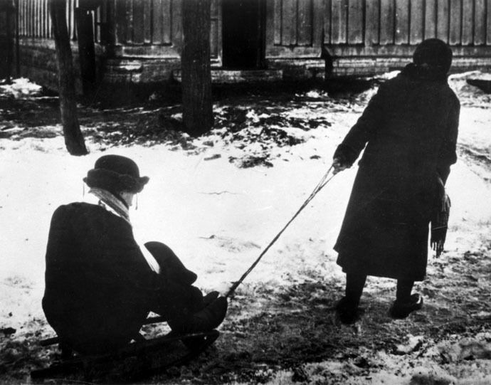 A woman sledging a starving husband in besieged Leningrad. (RIA Novosti/Israel Ozersky)