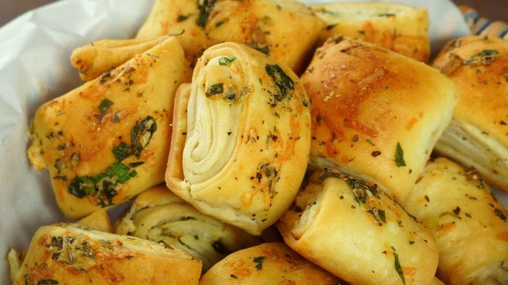 Receta con instrucciones en video: Perfecto Tentempié  Ingredientes: 2 láminas de masa hojaldrada, 2 cdas. de oliva, 2 cdas. de parmesano rallado, 1 cdita. de tomillo, 1 cdita. de orégano, 1 cdita. de romero, 1 cda. de perejil, 1 cda. de ajo picado, Sal y pimienta.
