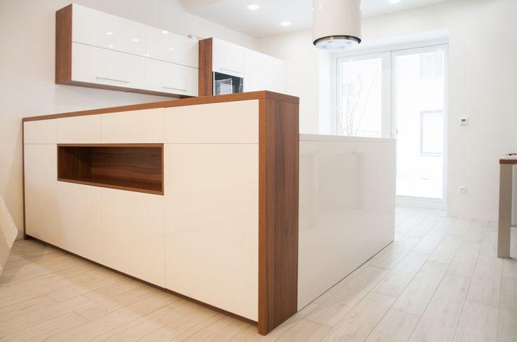 Při přestavbě rodinného domu byla stržena stěna dělící obývací část od kuchyně. Vznikla tak jedinečná prostorná místnost, která je elegantě oddělená barovým pultem. Kombinace ořechového dřevodekoru s lakovanými dvířky působí moderně a umožňuje snažší přechod kuchyně v nábytek obývacího pokoje. Rohy kuchyně jsou díky důmyslnému kování Magic Corner efektivně využity. Celkový dojem designové kuchyně doplňuje ostrůvkový odsavač Guzzanti v bílé barvě.