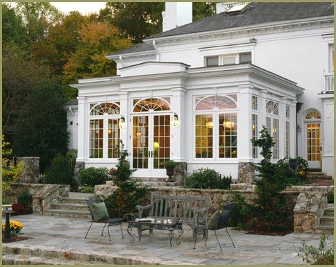 Conservatory with arched window accents and french doors leading to a stone patio area