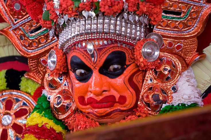 A Theyyam Dancer looks at a mirror, just before he slips into a trance and is transformed.