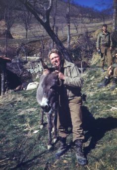 Schuck. Portrait of the photographer with a cigar in his mouth, he holds a donkey by its ears near an orchard in Italy. Unidentified Tenth Mountain Division soldiers look on in the background. All are wearing khaki uniforms and boots. Date	March 1945. Creator(s)	Molenaar, C. M. (Cornelius M.). Is Part Of 10th Mountain Division Resource Center Collection. Courtesy: Western History/Genealogy Department, Denver Public Library, Denver, Colorado (USA). Pin by Paolo Marzioli